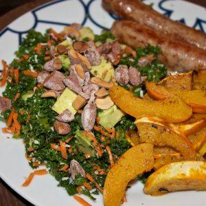 Fennikelpølser, hvidløgsbagt græskar og grønkålssalat med gulerod, avocado og saltmandler